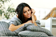 Happy young woman lying on the floor with pillows Stock Photo