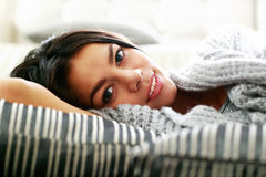 Happy young woman lying on the floor with pillows Stock Image