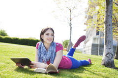 Happy young woman lying on grass  listening to music and enjoyi Stock Photos