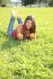Happy young woman lying in the grass with oranges Royalty Free Stock Photos