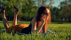 Happy Young Woman Lying on Green Lawn and Talking on the Phone or Smartphone. stock video footage