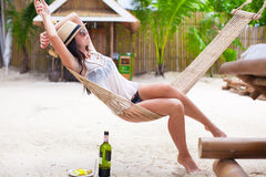 Happy young woman lying in hammock on tropical Royalty Free Stock Image