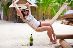 Happy young woman lying in hammock on tropical Royalty Free Stock Images