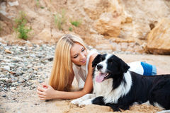 Happy young woman lying with her dog on the beach Stock Image