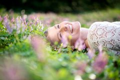 Happy young woman lying in meadow of flowers Royalty Free Stock Images