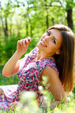 Happy young woman lying in a meadow on a warm summer day Royalty Free Stock Image