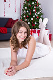 Happy young woman lying near decorated Christmas tree Royalty Free Stock Photos