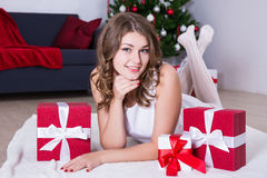 Happy young woman lying near decorated Christmas tree with gifts Royalty Free Stock Photo