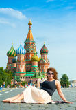 Happy young woman lying on Red Square Stock Image