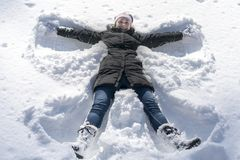 happy young woman lying on snow fur in wintertime. Young happy woman kidding on snow in winter day stock photography