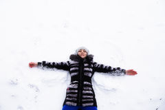 Happy young woman lying on snow fur in wintertime Stock Photography