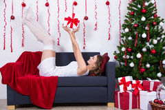 Happy young woman lying on sofa with decorated Christmas tree at Royalty Free Stock Photography