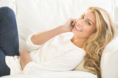 Happy Young Woman Lying On Sofa Royalty Free Stock Photos