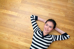 Happy young woman lying on wooden floor looking up. Happy young woman lying on parquet wooden floor looking up Stock Photo