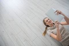 Happy young woman lying on wooden floor Stock Photography
