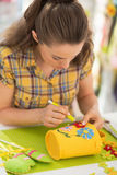 Happy young woman making easter decoration Stock Photo