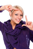 Happy young woman making a frame gesture. Happy attractive young blond woman making a frame gesture with her fingers framing her face as she uses her imagination Stock Photography