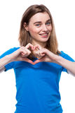 Happy young woman making a heart gesture Royalty Free Stock Photos