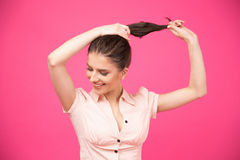 Happy young woman making her hair Stock Image