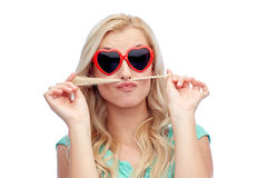 Happy young woman making mustache with her hair Royalty Free Stock Image