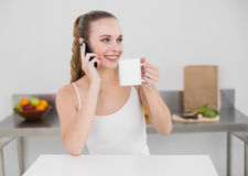 Happy young woman making a phone call and holding a mug Stock Photography