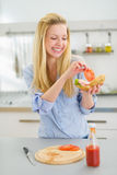 Happy young woman making sandwich in kitchen Royalty Free Stock Photo