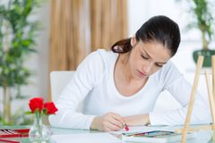 Happy young woman making sketches in art class. Woman royalty free stock images