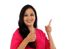 Happy young woman making thumbs up gesture against white Stock Photo
