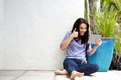 Happy young woman making video call using touchscreen tablet Royalty Free Stock Photo