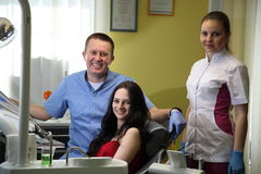 Happy young woman and male dentist after treatment in clinic. Stomatology. Dental office. Equipment for dentistry. The dentist`s workplace.Happy young woman and Stock Photos