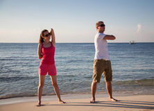 Happy young woman and man doing exercises on the sea coast Stock Photos
