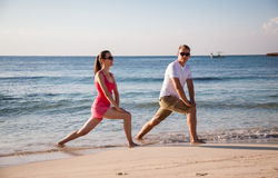 Happy young woman and man doing exercises on the sea coast Stock Image
