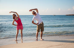 Happy young woman and man doing exercises Royalty Free Stock Images