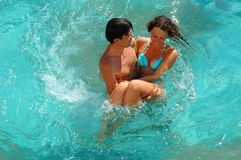 Happy young woman and man in pool Stock Photos