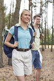 Happy young woman with man trekking in forest Royalty Free Stock Images