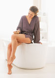 Happy young woman massaging leg in bathroom royalty free stock photography