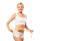 Happy young woman with a measuring tape over white Stock Images