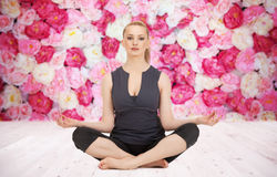 Happy young woman meditating in yoga lotus pose Stock Images