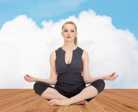 Happy young woman meditating in yoga lotus pose Stock Image
