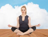 Happy young woman meditating in yoga lotus pose Royalty Free Stock Photos