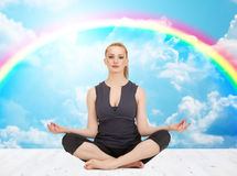 Happy young woman meditating in yoga lotus pose Stock Photography