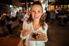 Happy young woman at Mercado San Miguel trying local delicacies. Portrait of happy young woman in white shirt at Mercado San Miguel trying local delicacies royalty free stock photo