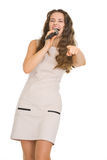 Happy woman with microphone pointing in camera Stock Image