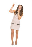 Happy young woman with microphone pointing up Stock Photography