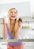Happy young woman with milk and chocolate muffin Royalty Free Stock Image