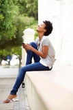 Happy young woman with mobile phone sitting by a street. Side portrait of happy young woman sitting by a street with a mobile phone Royalty Free Stock Photo