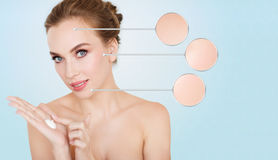 Happy young woman with moisturizing cream on hand Stock Photos