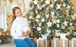 Happy young woman on morning at Christmas tree with gifts Stock Photo