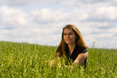 Happy young woman on nature. Happy young woman walking in an oats field Royalty Free Stock Photo