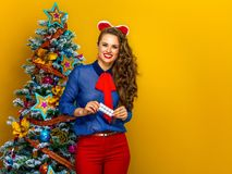 Happy young woman near Christmas tree holding pack of pills. Festive season. Portrait of happy young woman near Christmas tree isolated on yellow background Royalty Free Stock Image